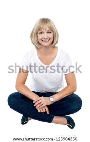 Smiling middle aged woman sitting on the floor, studio shot over white. - stock photo