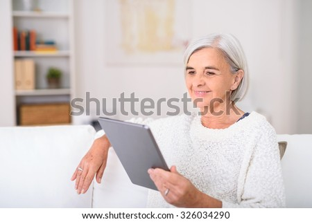 Smiling Middle Aged Woman Using a Tablet Computer While Relaxing at the Living Room. - stock photo