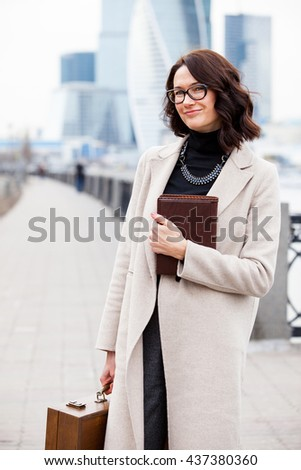 smiling middle-aged woman with glasses on his face, with books and wooden case in their hands on open air - stock photo