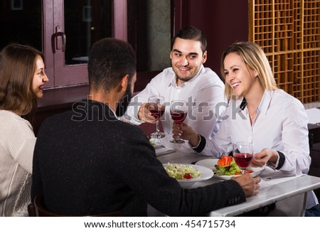 smiling middle class american people enjoying food in cafe and talking - stock photo