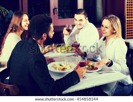 smiling middle class european people enjoying food in cafe and talking