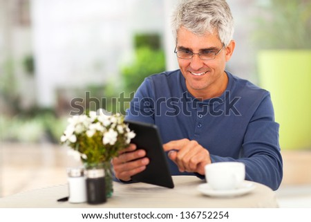 smiling middle ged man surfing the internet using tablet computer at home - stock photo