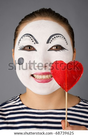 Smiling mime with the heart formed lollipop looking to the camera