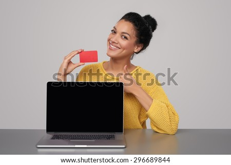 Smiling mixed race african american - caucasian woman showing blank black laptop computer screen and blank credit card, sitting at table and gesturing thumb up, over gray background - stock photo