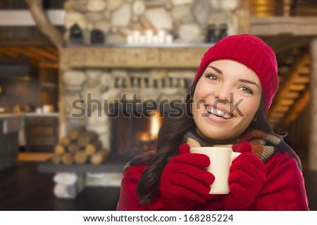 Smiling Mixed Race Girl Enjoying Warm Fireplace and Holding Mug of Cocoa or Hot Tea. - stock photo