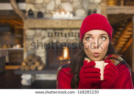 Smiling Mixed Race Girl Looking to The Side Enjoying a Warm Fireplace and Holding Mug of Cocoa or Hot Tea. - stock photo