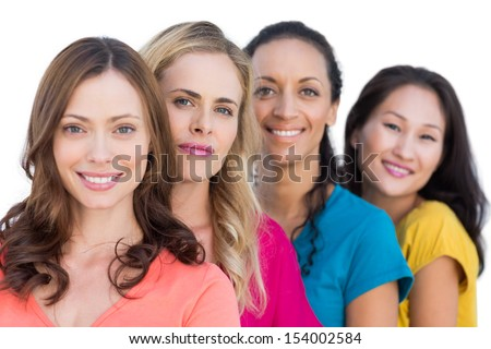 Smiling models in a line posing with colorful t shirts on white background