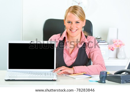Smiling modern business woman sitting at office desk and showing laptop with blank screen - stock photo