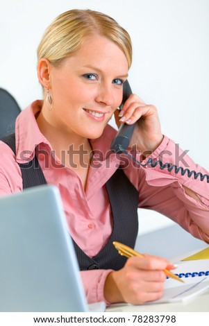 Smiling modern business woman sitting at office desk and talking on phone