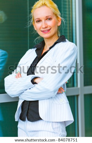 Smiling modern business woman standing near office building