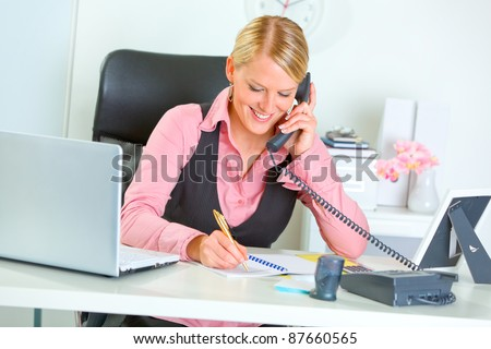 Smiling modern business woman talking phone and writing at notepad - stock photo