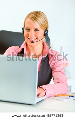 Smiling modern business woman with headset working on laptop - stock photo