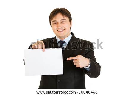 Smiling modern businessman pointing finger at empty white  paper isolated on white