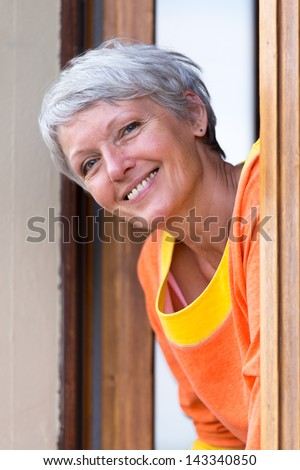 Smiling modern mature woman with grey hairs looking from the window. - stock photo