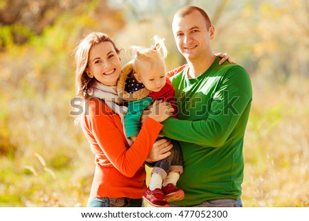 Smiling mom and dad hold their curious little daughter on their arms while posing in the park