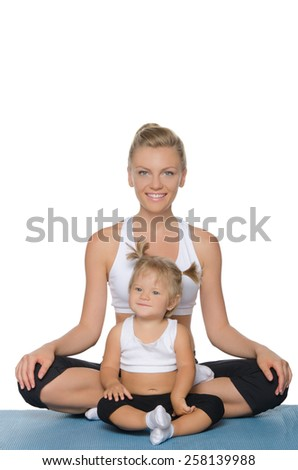 Smiling mom and daughter doing yoga on blue mat - stock photo