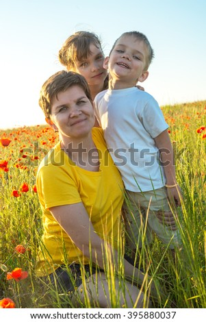 Smiling mom and her children in a meadow with blooming poppies. Happy spring day.