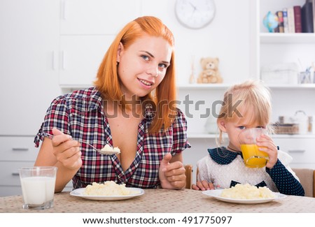 smiling mom eating porridge and feeding small girl indoors