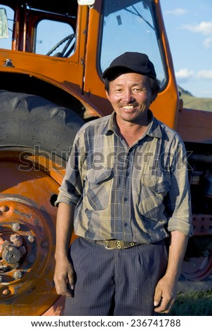 Smiling Mongolian farmer standing next to the tractor. - stock photo