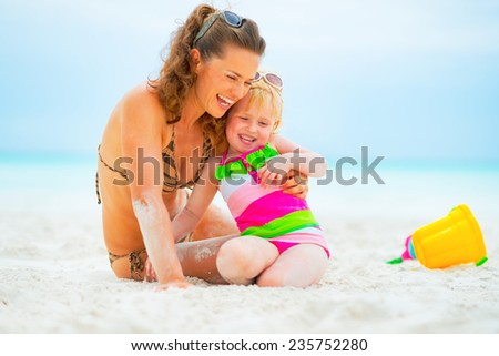 Smiling mother and baby girl playing on beach - stock photo