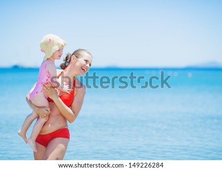Smiling mother and baby on sea background looking on copy space - stock photo
