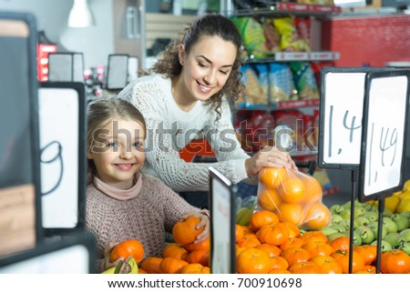 smiling mother and blonde daughter buying mandarins in shop. focus on girl