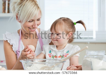 Smiling mother and child baking cookies in the kitchen - stock photo