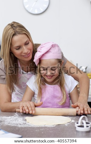 Smiling mother and daughter baking biscuits in the kitchen - stock photo