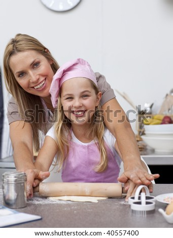 Smiling mother and daughter baking Christmas cookies in the kitchen - stock photo