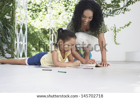 Smiling mother and daughter drawing with crayons on porch - stock photo