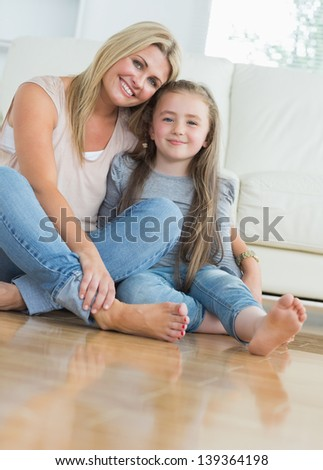 Smiling mother and daughter embracing on living room floor - stock photo