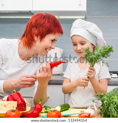 Smiling Mother and daughter in the kitchen with vegetables - stock photo