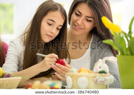 smiling mother and daughter kid paint Easter eggs - stock photo