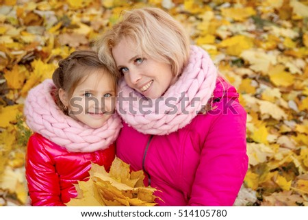 Smiling mother and daughter looking up on autumn background
