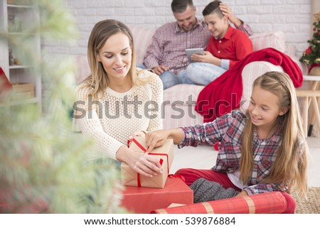 Smiling mother and daughter packing Christmas gifts on the floor