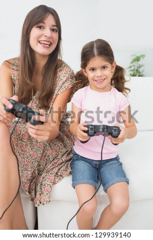 Smiling mother and daughter playing video games on the couch - stock photo