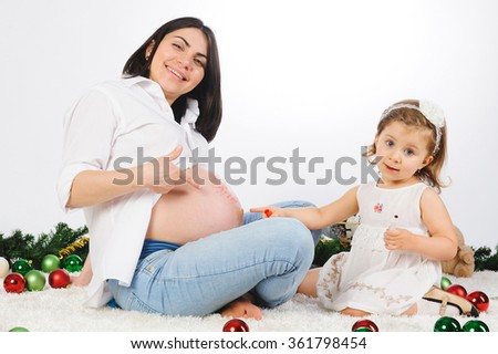 smiling mother and daughter pointing at belly with finger - stock photo