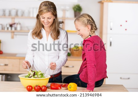 Smiling mother and daughter preparing a salad together in the kitchen as the little girl sits on the wooden counter top watching as Mum tosses the salad - stock photo