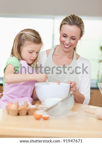 Smiling mother and daughter preparing dough for cookies togehter - stock photo