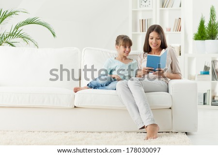 Smiling mother and daughter reading a book together in the living room.