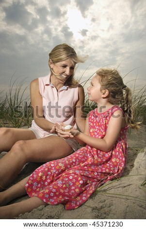 Smiling mother and daughter sit on sand looking at seashells together. Vertical shot. - stock photo