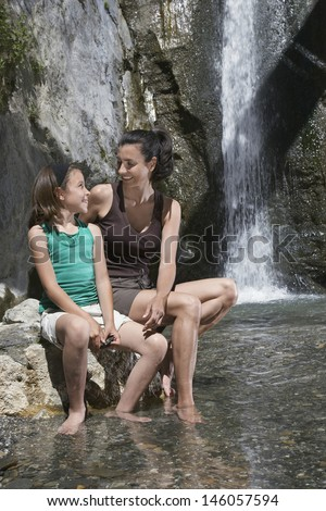 Smiling mother and daughter sitting on rock by waterfall