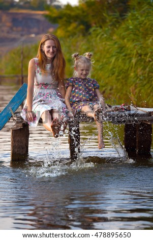 smiling mother and daughter sitting on the pier warm autumn day dangling his legs in the water and splash in the foreground