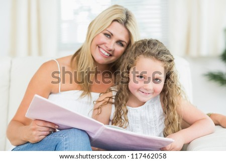 Smiling mother and daughter sitting on the sofa with a book - stock photo