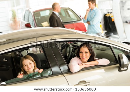 Smiling mother and daughter trying car in dealership - stock photo