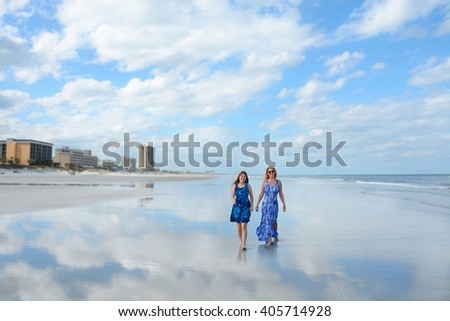 Smiling mother and daughter walking on beautiful beach, hotels in the background, reflection of beautiful sky and clouds in the water on the beach, Jacksonville, Florida. - stock photo