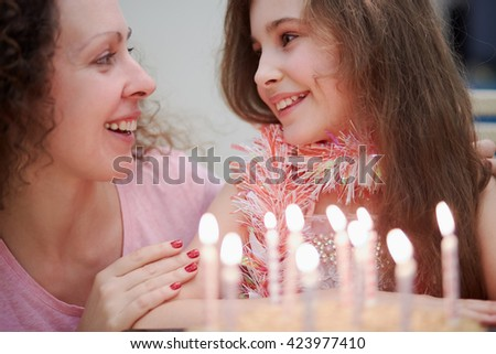 Smiling mother and daughter with birthday cake and burning candles.