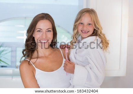 Smiling mother and daughter with toothbrush in the bathroom at home - stock photo