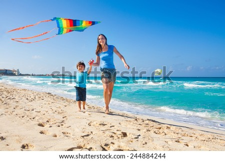Smiling mother and happy son holding arms and flying kite in the sky during sunny day on beach coast and ocean waves - stock photo