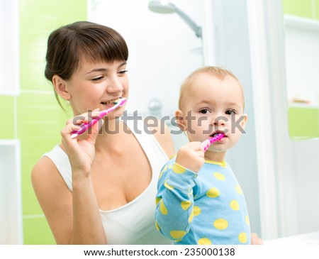 smiling mother and kid daughter brushing teeth in bath room - stock photo